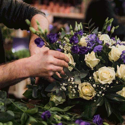 Paars-wit rouwstuk gemaakt door vakman bij Bloemenweelde