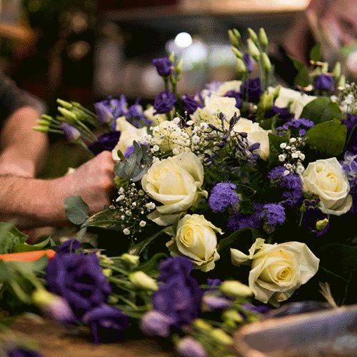 Paars-wit rouwstuk gemaakt door vakbloemist Bloemenweelde